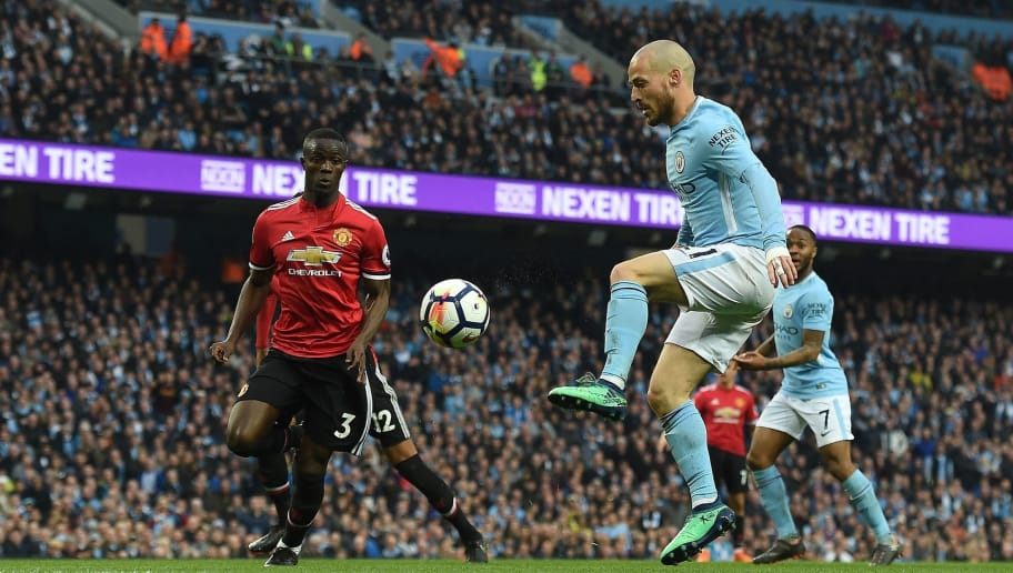 Manchester City's Spanish midfielder David Silva (R) vies with Manchester United's Ivorian defender Eric Bailly during the English Premier League football match between Manchester City and Manchester United at the Etihad Stadium in Manchester, north west England, on April 7, 2018. / AFP PHOTO / PAUL ELLIS / RESTRICTED TO EDITORIAL USE. No use with unauthorized audio, video, data, fixture lists, club/league logos or 'live' services. Online in-match use limited to 75 images, no video emulation. No use in betting, games or single club/league/player publications.  /         (Photo credit should read PAUL ELLIS/AFP/Getty Images)