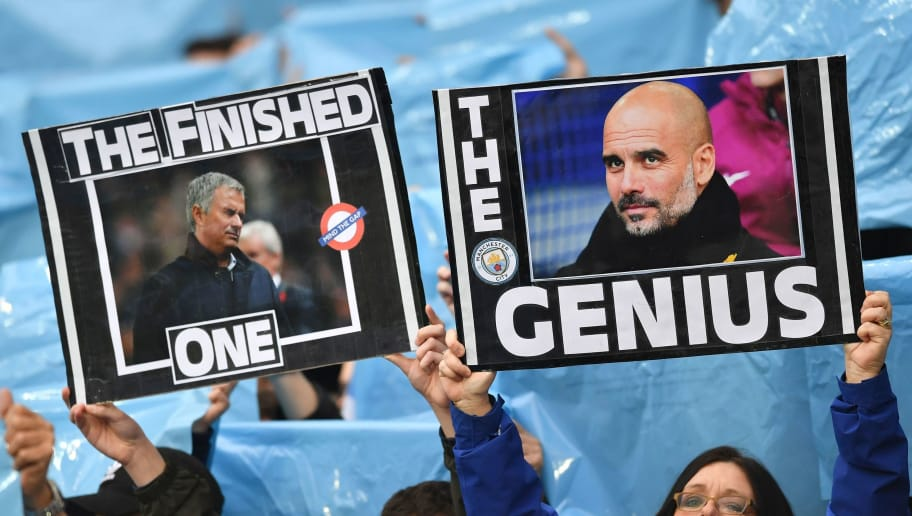 Manchester City fans hold up placards showing the faces of Manchester City's Spanish manager Pep Guardiola (R) and Manchester United's Portuguese manager Jose Mourinho (L) during the English Premier League football match between Manchester City and Manchester United at the Etihad Stadium in Manchester, north west England, on April 7, 2018. / AFP PHOTO / Ben STANSALL / RESTRICTED TO EDITORIAL USE. No use with unauthorized audio, video, data, fixture lists, club/league logos or 'live' services. Online in-match use limited to 75 images, no video emulation. No use in betting, games or single club/league/player publications.  /         (Photo credit should read BEN STANSALL/AFP/Getty Images)