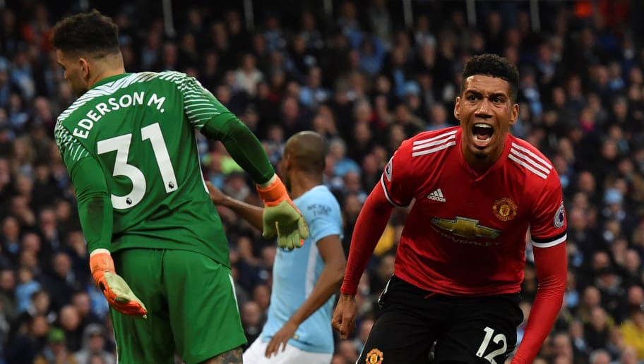 Manchester United's English defender Chris Smalling (R) celebrates scoring his team's third goal during the English Premier League football match between Manchester City and Manchester United at the Etihad Stadium in Manchester, north west England, on April 7, 2018. Manchester United won the match 3-2. / AFP PHOTO / Ben STANSALL / RESTRICTED TO EDITORIAL USE. No use with unauthorized audio, video, data, fixture lists, club/league logos or 'live' services. Online in-match use limited to 75 images, no video emulation. No use in betting, games or single club/league/player publications.  /         (Photo credit should read BEN STANSALL/AFP/Getty Images)