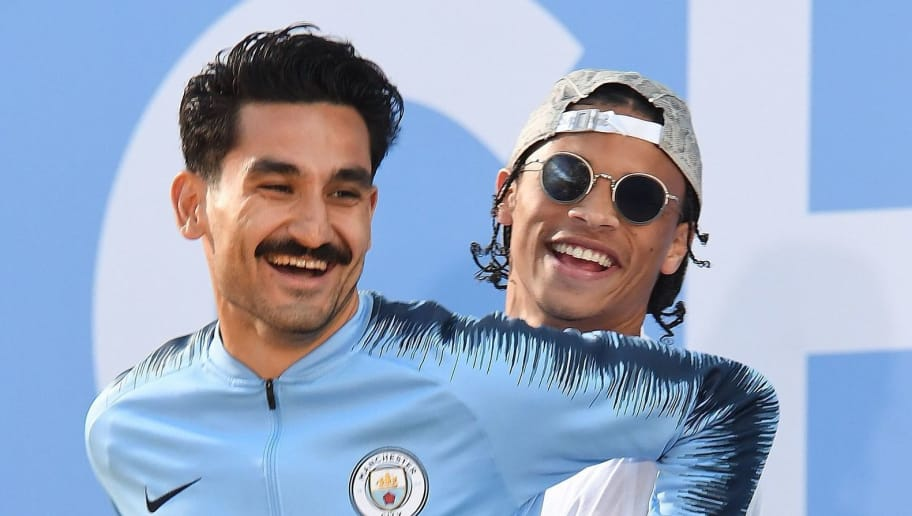 Manchester City's German midfielder Leroy Sane (R) lifts Manchester City's German midfielder Ilkay Gundogan as htey attend an event for fans with members of the Manchester City football team following an open-top bus parade through Manchester, northern England on May 14, 2018 to celebrate winning the 2018 Premier League title. - Manchester City set the seal on a record-breaking season by becoming the first side in English top flight history to hit 100 points with victory at Southampton on Sunday. City also added another landmark by winning the league by a record 19 points from local rivals Manchester United. (Photo by Paul ELLIS / AFP)        (Photo credit should read PAUL ELLIS/AFP/Getty Images)