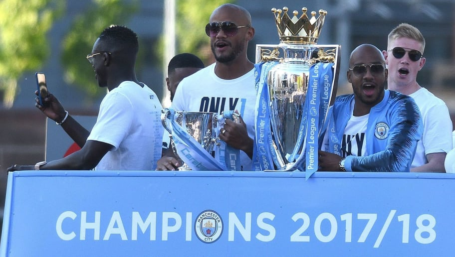 Manchester City's English midfielder Fabian Delph (2R) holds up the Preimer League trophy as Manchester City's Belgian defender Vincent Kompany (2L) holds up the English League Cup trophy to fans as the Manchester City team take part in an open-top bus parade through Manchester, northern England on May 14, 2018 to celebrate winning the 2018 Premier League title. - Manchester City set the seal on a record-breaking season by becoming the first side in English top flight history to hit 100 points with victory at Southampton on Sunday. City also added another landmark by winning the league by a record 19 points from local rivals Manchester United. (Photo by Oli SCARFF / AFP)        (Photo credit should read OLI SCARFF/AFP/Getty Images)