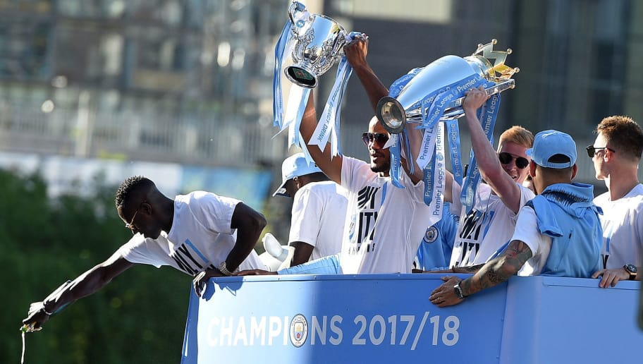 Manchester City's Belgian midfielder Kevin De Bruyne (3R) holds up the Preimer Leagu trophy as Manchester City's Belgian defender Vincent Kompany (C) holds up the English League Cup trophy to fans as the Manchester City team take part in an open-top bus parade through Manchester, northern England on May 14, 2018 to celebrate winning the 2018 Premier League title. - Manchester City set the seal on a record-breaking season by becoming the first side in English top flight history to hit 100 points with victory at Southampton on Sunday. City also added another landmark by winning the league by a record 19 points from local rivals Manchester United. (Photo by Oli SCARFF / AFP)        (Photo credit should read OLI SCARFF/AFP/Getty Images)