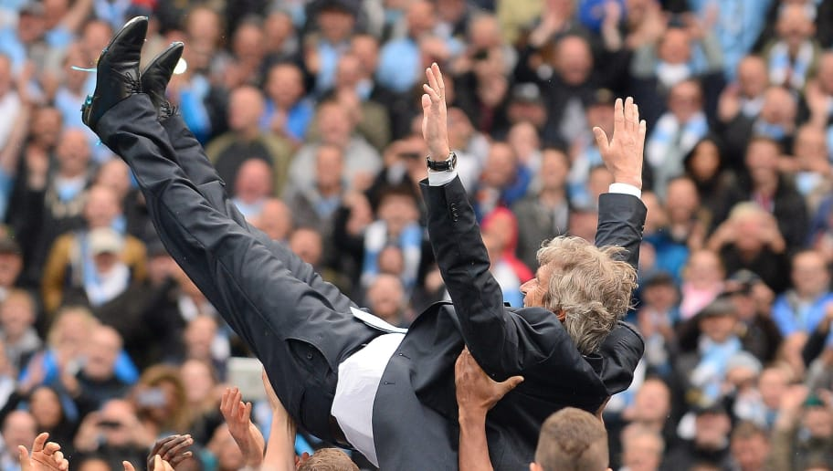 Manchester City's Chilean manager Manuel Pellegrini is thrown in the air by his players as they celebrate after winning the Premiership title following the English Premier League football match between Manchester City and West Ham United at the Etihad Stadium in Manchester on May 11, 2014.  AFP PHOTO/ANDREW YATES RESTRICTED TO EDITORIAL USE. No use with unauthorized audio, video, data, fixture lists, club/league logos or live services. Online in-match use limited to 45 images, no video emulation. No use in betting, games or single club/league/player publications.        (Photo credit should read ANDREW YATES/AFP/Getty Images)