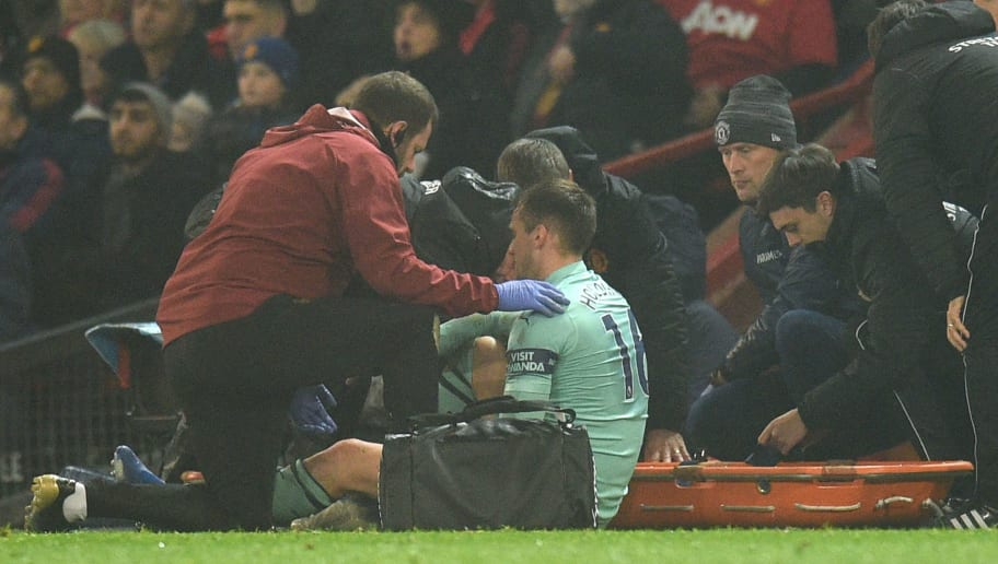 Arsenal's English defender Rob Holding (C) recieves attention at the side of the pitch for an injury before being stretchered off during the English Premier League football match between Manchester United and Arsenal at Old Trafford in Manchester, north west England, on December 5, 2018. (Photo by Oli SCARFF / AFP) / RESTRICTED TO EDITORIAL USE. No use with unauthorized audio, video, data, fixture lists, club/league logos or 'live' services. Online in-match use limited to 120 images. An additional 40 images may be used in extra time. No video emulation. Social media in-match use limited to 120 images. An additional 40 images may be used in extra time. No use in betting publications, games or single club/league/player publications. /         (Photo credit should read OLI SCARFF/AFP/Getty Images)