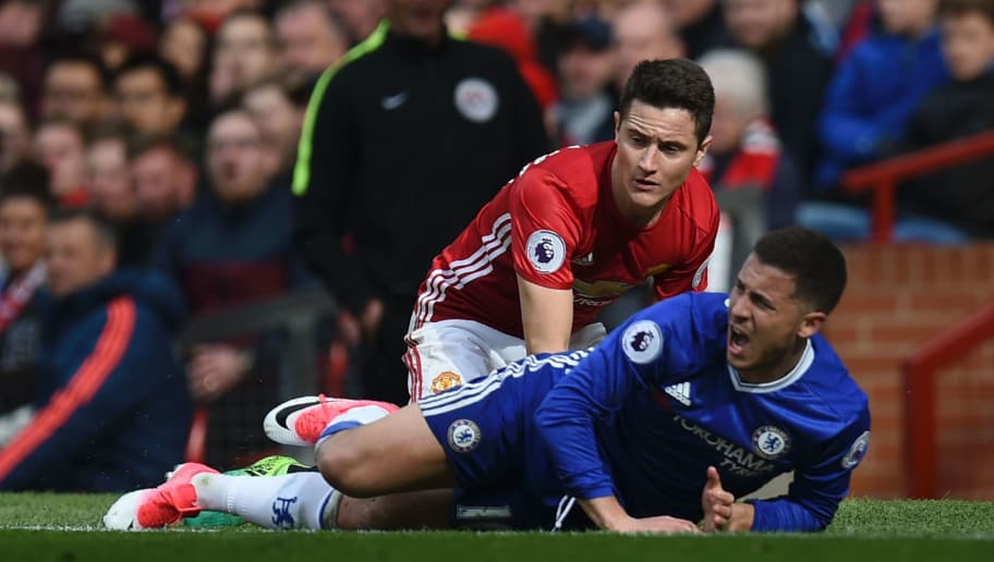 Manchester United's Spanish midfielder Ander Herrera (L) goes down in a challenge with Chelsea's Belgian midfielder Eden Hazard (R) during the English Premier League football match between Manchester United and Chelsea at Old Trafford in Manchester, north west England, on April 16, 2017. / AFP PHOTO / Oli SCARFF / RESTRICTED TO EDITORIAL USE. No use with unauthorized audio, video, data, fixture lists, club/league logos or 'live' services. Online in-match use limited to 75 images, no video emulation. No use in betting, games or single club/league/player publications.  /         (Photo credit should read OLI SCARFF/AFP/Getty Images)