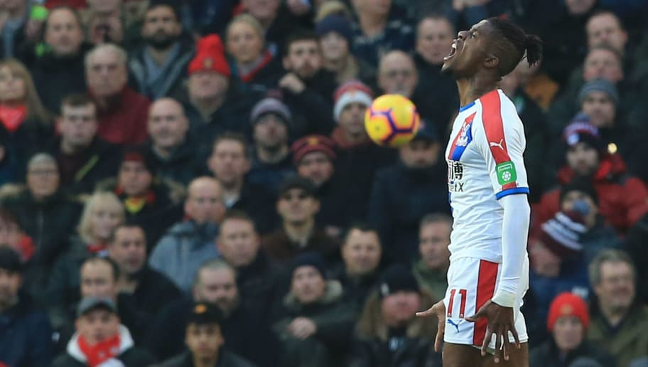 Crystal Palace's Ivorian striker Wilfried Zaha (R) reacts during the English Premier League football match between Manchester United and Crystal Palace at Old Trafford in Manchester, north west England, on November 24, 2018. (Photo by Lindsey PARNABY / AFP) / RESTRICTED TO EDITORIAL USE. No use with unauthorized audio, video, data, fixture lists, club/league logos or 'live' services. Online in-match use limited to 120 images. An additional 40 images may be used in extra time. No video emulation. Social media in-match use limited to 120 images. An additional 40 images may be used in extra time. No use in betting publications, games or single club/league/player publications. /         (Photo credit should read LINDSEY PARNABY/AFP/Getty Images)