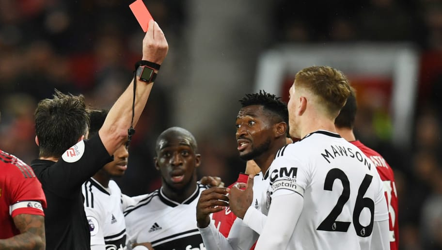 Fulham's Cambodian midfielder Andre-Frank Zambo Anguissa (R) receives a red card during the English Premier League football match between Manchester United and Fulham at Old Trafford in Manchester, north west England, on December 8, 2018. (Photo by Paul ELLIS / AFP) / RESTRICTED TO EDITORIAL USE. No use with unauthorized audio, video, data, fixture lists, club/league logos or 'live' services. Online in-match use limited to 120 images. An additional 40 images may be used in extra time. No video emulation. Social media in-match use limited to 120 images. An additional 40 images may be used in extra time. No use in betting publications, games or single club/league/player publications. /         (Photo credit should read PAUL ELLIS/AFP/Getty Images)
