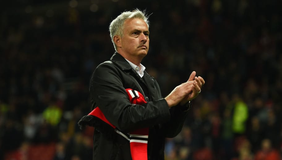 Manchester United's Portuguese manager Jose Mourinho holds a team scarf that was thrown from the crowd as he stands on the pitch applauding the homes fans that stayed until the end after the English Premier League football match between Manchester United and Tottenham Hotspur at Old Trafford in Manchester, north west England, on August 27, 2018. (Photo by Oli SCARFF / AFP) / RESTRICTED TO EDITORIAL USE. No use with unauthorized audio, video, data, fixture lists, club/league logos or 'live' services. Online in-match use limited to 120 images. An additional 40 images may be used in extra time. No video emulation. Social media in-match use limited to 120 images. An additional 40 images may be used in extra time. No use in betting publications, games or single club/league/player publications. /         (Photo credit should read OLI SCARFF/AFP/Getty Images)