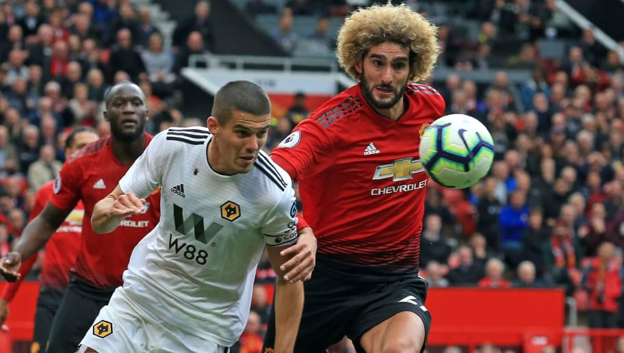 Manchester United's Belgian midfielder Marouane Fellaini vies with Wolverhampton Wanderers' English midfielder Conor Coady (2nd L) during the English Premier League football match between Manchester United and Wolverhampton Wanderers at Old Trafford in Manchester, north west England, on September 22, 2018. (Photo by Lindsey PARNABY / AFP) / RESTRICTED TO EDITORIAL USE. No use with unauthorized audio, video, data, fixture lists, club/league logos or 'live' services. Online in-match use limited to 120 images. An additional 40 images may be used in extra time. No video emulation. Social media in-match use limited to 120 images. An additional 40 images may be used in extra time. No use in betting publications, games or single club/league/player publications. /         (Photo credit should read LINDSEY PARNABY/AFP/Getty Images)