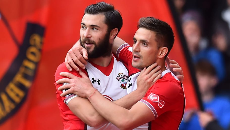 Southampton's Serbian midfielder Dusan Tadic (R) celebrates with Southampton's English striker Charlie Austin for scoring the opening goal during the English Premier League football match between Southampton and Bournemouth at St Mary's Stadium in Southampton, southern England on April 28, 2018. (Photo by Glyn KIRK / AFP) / RESTRICTED TO EDITORIAL USE. No use with unauthorized audio, video, data, fixture lists, club/league logos or 'live' services. Online in-match use limited to 75 images, no video emulation. No use in betting, games or single club/league/player publications. /         (Photo credit should read GLYN KIRK/AFP/Getty Images)