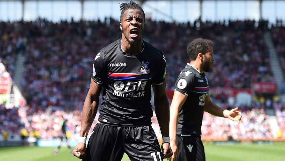 Crystal Palace's Ivorian striker Wilfried Zaha (L) celebrates after scoring the equalising goal during the English Premier League football match between Stoke City and Crystal Palace at the Bet365 Stadium in Stoke-on-Trent, central England on May 5, 2018. (Photo by Oli SCARFF / AFP) / RESTRICTED TO EDITORIAL USE. No use with unauthorized audio, video, data, fixture lists, club/league logos or 'live' services. Online in-match use limited to 75 images, no video emulation. No use in betting, games or single club/league/player publications. /         (Photo credit should read OLI SCARFF/AFP/Getty Images)