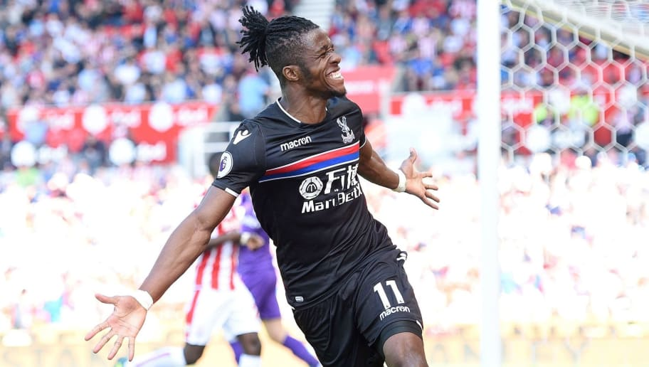 Crystal Palace's Ivorian striker Wilfried Zaha celebrates after scoring the equalising goal during the English Premier League football match between Stoke City and Crystal Palace at the Bet365 Stadium in Stoke-on-Trent, central England on May 5, 2018. (Photo by Oli SCARFF / AFP) / RESTRICTED TO EDITORIAL USE. No use with unauthorized audio, video, data, fixture lists, club/league logos or 'live' services. Online in-match use limited to 75 images, no video emulation. No use in betting, games or single club/league/player publications. /         (Photo credit should read OLI SCARFF/AFP/Getty Images)