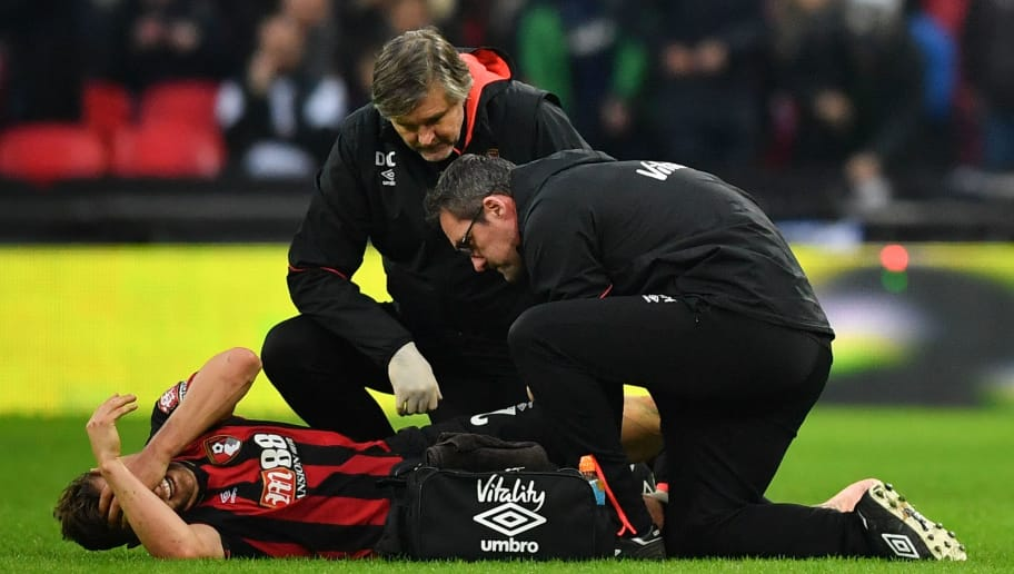 Bournemouth's English defender Simon Francis gets attention on the field for an injury during the English Premier League football match between Tottenham Hotspur and Bournemouth at Wembley Stadium in London, on December 26, 2018. (Photo by Ben STANSALL / AFP) / RESTRICTED TO EDITORIAL USE. No use with unauthorized audio, video, data, fixture lists, club/league logos or 'live' services. Online in-match use limited to 120 images. An additional 40 images may be used in extra time. No video emulation. Social media in-match use limited to 120 images. An additional 40 images may be used in extra time. No use in betting publications, games or single club/league/player publications. /         (Photo credit should read BEN STANSALL/AFP/Getty Images)