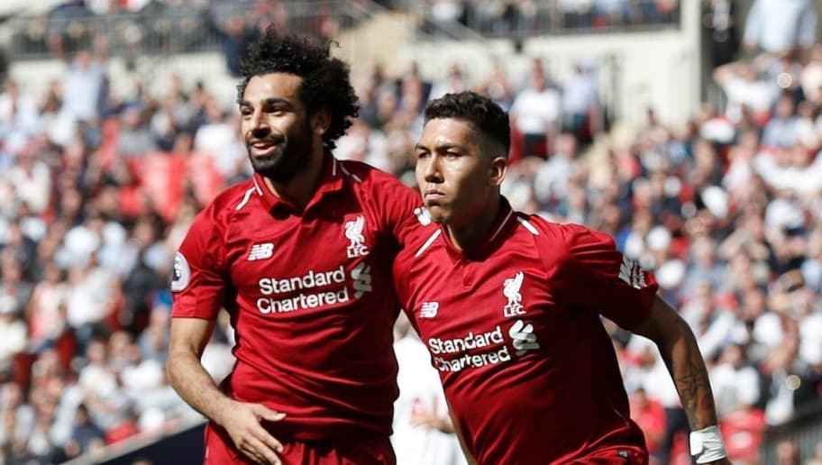 Liverpool's Brazilian midfielder Roberto Firmino (R) celebrates with Liverpool's Egyptian midfielder Mohamed Salah after scoring their second goal during the English Premier League football match between Tottenham Hotspur and Liverpool at Wembley Stadium in London, on September 15, 2018. (Photo by Adrian DENNIS / IKIMAGES / AFP) / RESTRICTED TO EDITORIAL USE. No use with unauthorized audio, video, data, fixture lists, club/league logos or 'live' services. Online in-match use limited to 45 images, no video emulation. No use in betting, games or single club/league/player publications.        (Photo credit should read ADRIAN DENNIS/AFP/Getty Images)