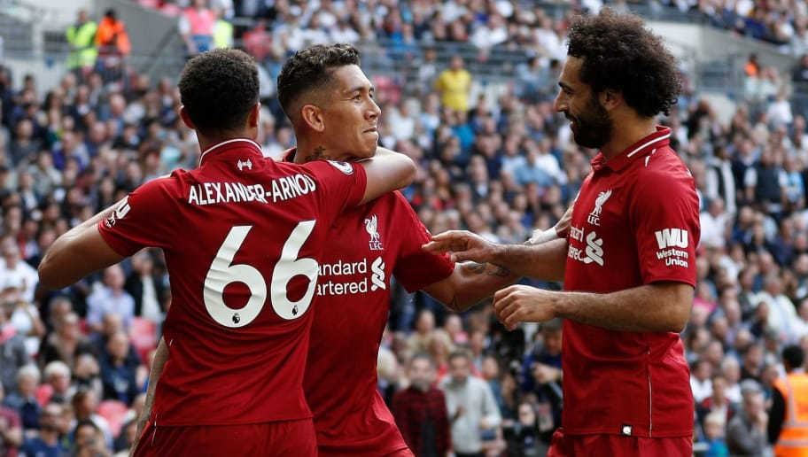 Liverpool's Brazilian midfielder Roberto Firmino (C) celebrates after scoring their second goal with Liverpool's English defender Trent Alexander-Arnold (L) and Liverpool's Egyptian midfielder Mohamed Salah during the English Premier League football match between Tottenham Hotspur and Liverpool at Wembley Stadium in London, on September 15, 2018. (Photo by Adrian DENNIS / AFP) / RESTRICTED TO EDITORIAL USE. No use with unauthorized audio, video, data, fixture lists, club/league logos or 'live' services. Online in-match use limited to 120 images. An additional 40 images may be used in extra time. No video emulation. Social media in-match use limited to 120 images. An additional 40 images may be used in extra time. No use in betting publications, games or single club/league/player publications. /         (Photo credit should read ADRIAN DENNIS/AFP/Getty Images)