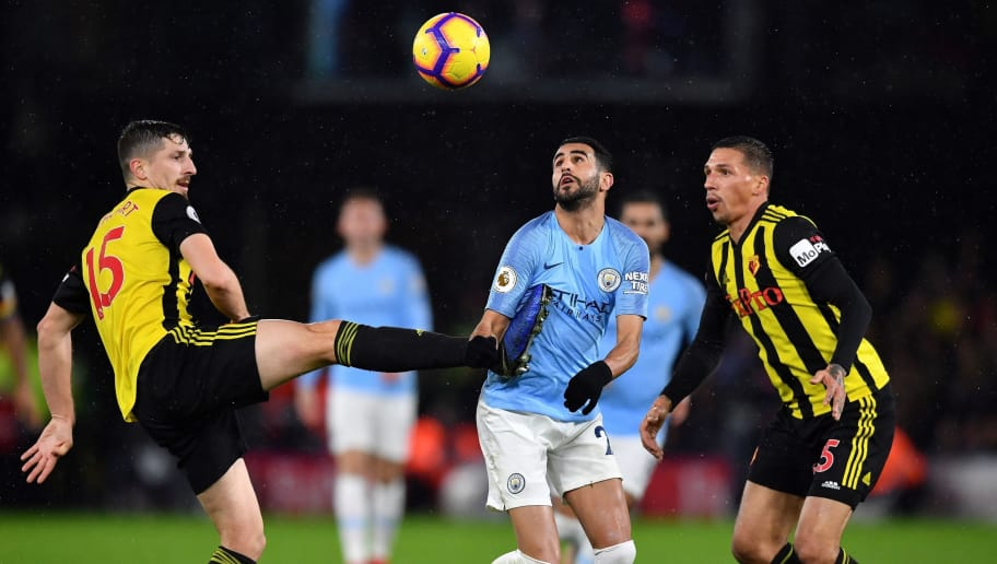 Manchester City's Algerian midfielder Riyad Mahrez (C) vies with Watford's Northern Irish defender Craig Cathcart (L) during the English Premier League football match between Watford and Manchester City at Vicarage Road Stadium in Watford, north of London on December 4, 2018. (Photo by Ben STANSALL / AFP) / RESTRICTED TO EDITORIAL USE. No use with unauthorized audio, video, data, fixture lists, club/league logos or 'live' services. Online in-match use limited to 120 images. An additional 40 images may be used in extra time. No video emulation. Social media in-match use limited to 120 images. An additional 40 images may be used in extra time. No use in betting publications, games or single club/league/player publications. /         (Photo credit should read BEN STANSALL/AFP/Getty Images)