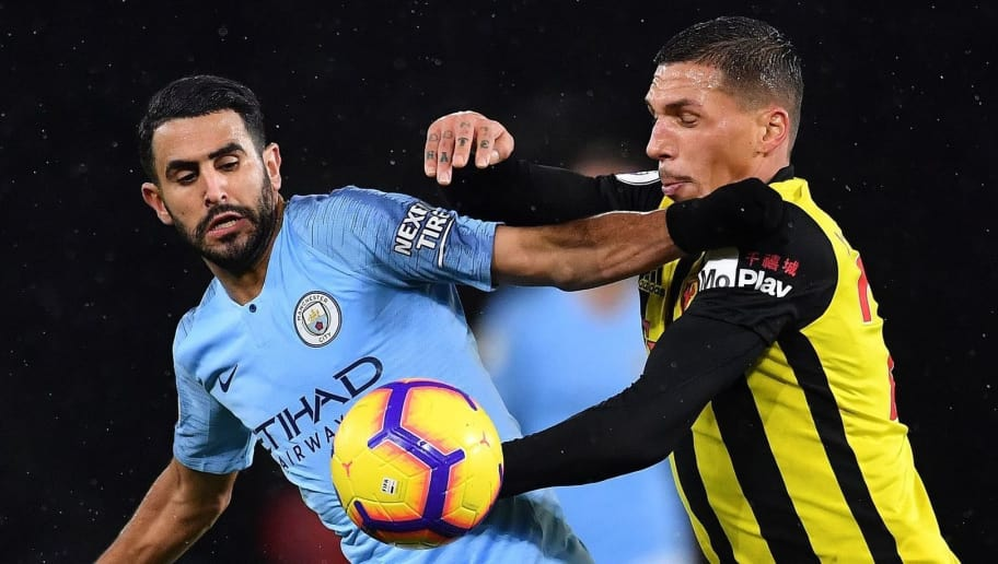 Manchester City's Algerian midfielder Riyad Mahrez (L) voes with Watford's German-born Greek midfielder Jose Holebas during the English Premier League football match between Watford and Manchester City at Vicarage Road Stadium in Watford, north of London on December 4, 2018. (Photo by Ben STANSALL / AFP) / RESTRICTED TO EDITORIAL USE. No use with unauthorized audio, video, data, fixture lists, club/league logos or 'live' services. Online in-match use limited to 120 images. An additional 40 images may be used in extra time. No video emulation. Social media in-match use limited to 120 images. An additional 40 images may be used in extra time. No use in betting publications, games or single club/league/player publications. /         (Photo credit should read BEN STANSALL/AFP/Getty Images)