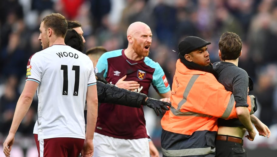 West Ham United's Welsh defender James Collins (C) confronts a pitch invader during the English Premier League football match between West Ham United and Burnley at The London Stadium, in east London on March 10, 2018. / AFP PHOTO / Ben STANSALL / RESTRICTED TO EDITORIAL USE. No use with unauthorized audio, video, data, fixture lists, club/league logos or 'live' services. Online in-match use limited to 75 images, no video emulation. No use in betting, games or single club/league/player publications.  /         (Photo credit should read BEN STANSALL/AFP/Getty Images)