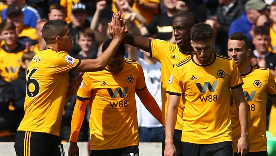 Wolverhampton Wanderers' French defender Willy Boly (C) celebrates with team-mates after scoring the opening goal during the English Premier League football match between Wolverhampton Wanderers and Manchester City at the Molineux stadium in Wolverhampton, central England on August 25, 2018. (Photo by Geoff CADDICK / AFP) / RESTRICTED TO EDITORIAL USE. No use with unauthorized audio, video, data, fixture lists, club/league logos or 'live' services. Online in-match use limited to 120 images. An additional 40 images may be used in extra time. No video emulation. Social media in-match use limited to 120 images. An additional 40 images may be used in extra time. No use in betting publications, games or single club/league/player publications. /         (Photo credit should read GEOFF CADDICK/AFP/Getty Images)