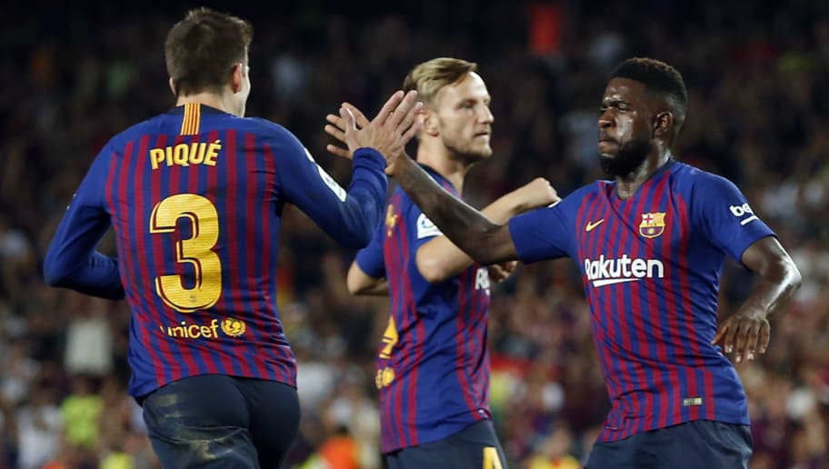 Barcelona's French defender Samuel Umtiti (R) congratulates Barcelona's Spanish defender Gerard Pique for his goal during the Spanish league football match between FC Barcelona and Girona FC at the Camp Nou stadium in Barcelona on September 23, 2018. (Photo by Pau Barrena / AFP)        (Photo credit should read PAU BARRENA/AFP/Getty Images)