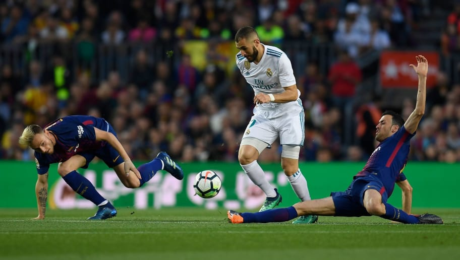 Real Madrid's French forward Karim Benzema (C) challenges Barcelona's Croatian midfielder Ivan Rakitic and Barcelona's Spanish midfielder Sergio Busquets (R) during the Spanish league football match between FC Barcelona and Real Madrid CF at the Camp Nou stadium in Barcelona on May 6, 2018. (Photo by LLUIS GENE / AFP)        (Photo credit should read LLUIS GENE/AFP/Getty Images)