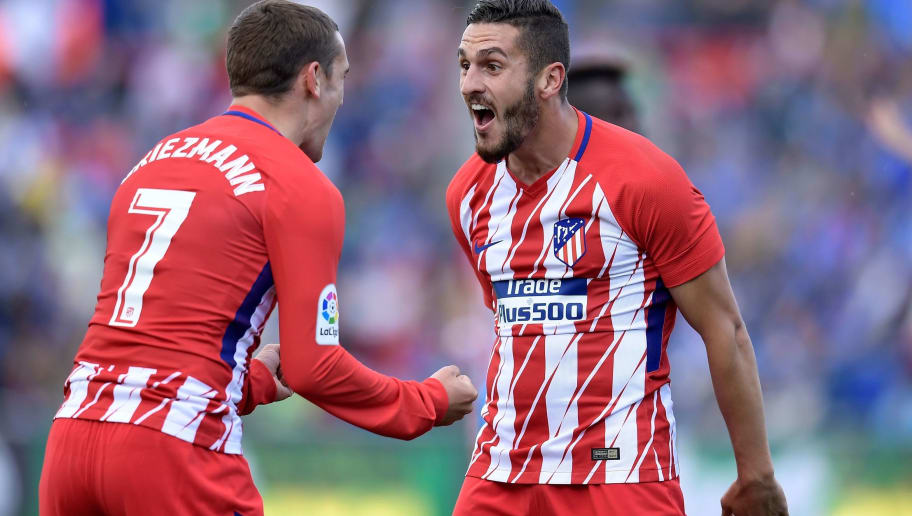 Atletico Madrid's Spanish midfield Koke (R) celebrates a goal with Atletico Madrid's French forward Antoine Griezmann during the Spanish league football match between Getafe and Atletico Madrid at the Coliseum Alfonso Perez stadium in Getafe on May 12, 2018. (Photo by OSCAR DEL POZO / AFP)        (Photo credit should read OSCAR DEL POZO/AFP/Getty Images)
