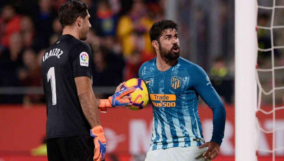 Atletico Madrid's Spanish forward Diego Costa celebrates next to Girona's Spanish goalkeeper Gorka Iraizoz (L) after scoring a goal during the Spanish league football match between Girona and Club Atletico de Madrid at the Montilivi stadium in Girona on December 2, 2018. (Photo by Josep LAGO / AFP)        (Photo credit should read JOSEP LAGO/AFP/Getty Images)