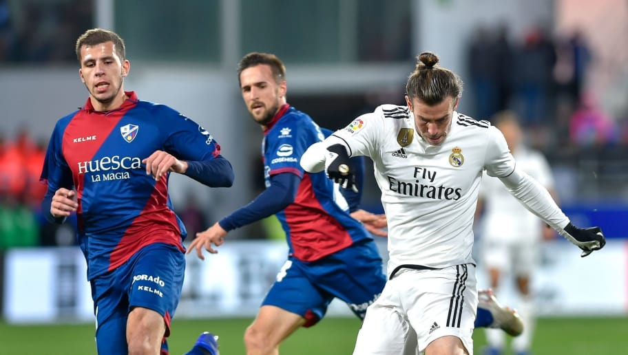 Real Madrid's Welsh forward Gareth Bale (R) kicks the ball during the Spanish league football match between SD Huesca and Real Madrid CF at the El Alcoraz stadium in Huesca, on December 9, 2018. (Photo by ANDER GILLENEA / AFP)        (Photo credit should read ANDER GILLENEA/AFP/Getty Images)