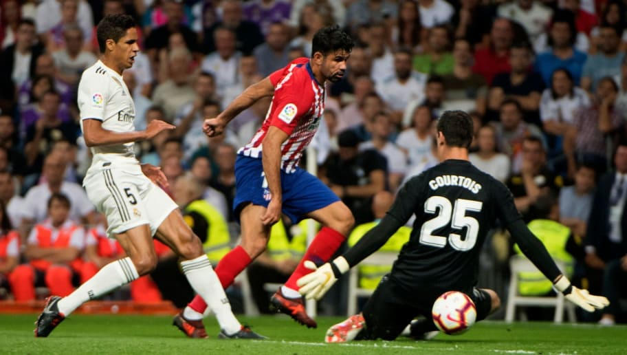 Real Madrid's French defender Raphael Varane (L) and Real Madrid's Belgian goalkeeper Thibaut Courtois vie with Atletico Madrid's Spanish forward Diego Costa (C) during the Spanish league football match between Real Madrid CF and Club Atletico de Madrid at the Santiago Bernabeu stadium in Madrid on September 29, 2018. (Photo by CURTO DE LA TORRE / AFP)        (Photo credit should read CURTO DE LA TORRE/AFP/Getty Images)