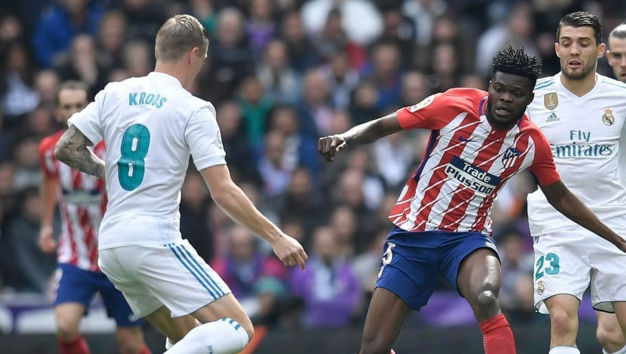 Atletico Madrid's Ghanaian midfielder Thomas (C) challenges Real Madrid's Croatian midfielder Mateo Kovacic (R) and Real Madrid's German midfielder Toni Kroos during the Spanish league football match between Real Madrid CF and Club Atletico de Madrid at the Santiago Bernabeu stadium in Madrid on April 8, 2018. / AFP PHOTO / GABRIEL BOUYS        (Photo credit should read GABRIEL BOUYS/AFP/Getty Images)