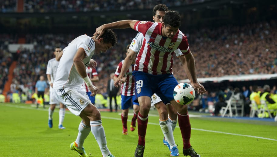 Real Madrid's Portuguese defender Pepe vies with Atletico Madrid's Brazilian forward Diego da Silva Costa during the Spanish league football match Real Madrid CF vs Club Atletico de Madrid at the Santiago Bernabeu stadium in Madrid on September 28, 2013.  AFP PHOTO/ DANI POZO        (Photo credit should read DANI POZO/AFP/Getty Images)