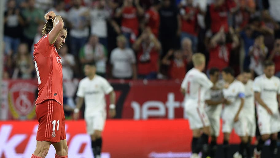 Real Madrid's Welsh forward Gareth Bale (L) reacts Sevilla's Portuguese forward Andre Silva's goal during the Spanish league football match Sevilla FC against Real Madrid CF at the Ramon Sanchez Pizjuan stadium in Seville on September 26, 2018. (Photo by CRISTINA QUICLER / AFP)        (Photo credit should read CRISTINA QUICLER/AFP/Getty Images)