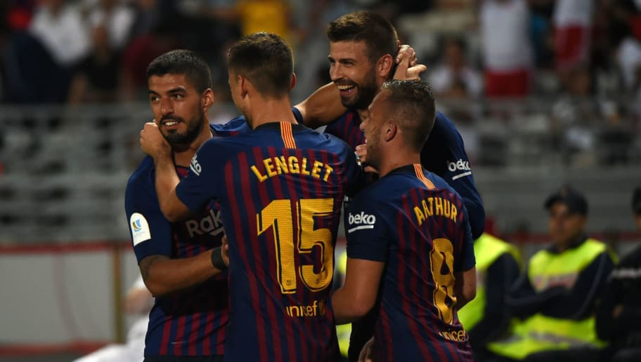 Barcelona's Spanish defender Gerard Pique (2nd-R) celebrates with his teammates (From L) Barcelona's Uruguayan forward Luis Suarez, Barcelona's French defender Clement Lenglet and Barcelona's Brazilian midfielder Arthur after scoring a goal during the Spanish Super Cup final between Sevilla and FC Barcelona at Ibn Batouta stadium in the Moroccan city of Tangiers on August 12, 2018. (Photo by FADEL SENNA / AFP)        (Photo credit should read FADEL SENNA/AFP/Getty Images)