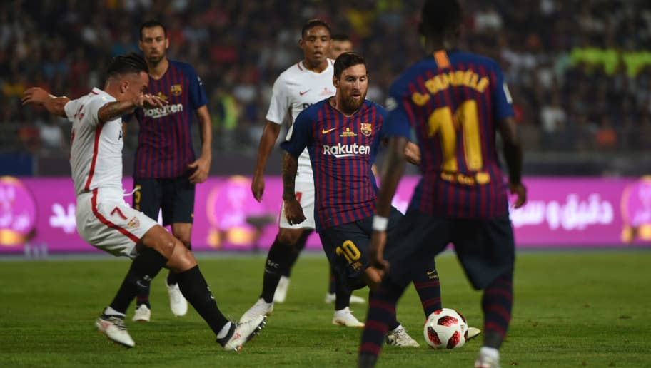 Barcelona's Argentinian forward Lionel Messi (2nd-R) passes the ball to Barcelona's French forward Ousmane Dembele (1st-R) during the Spanish Super Cup final between Sevilla and FC Barcelona at Ibn Batouta stadium in the Moroccan city of Tangiers on August 12, 2018. (Photo by FADEL SENNA / AFP)        (Photo credit should read FADEL SENNA/AFP/Getty Images)