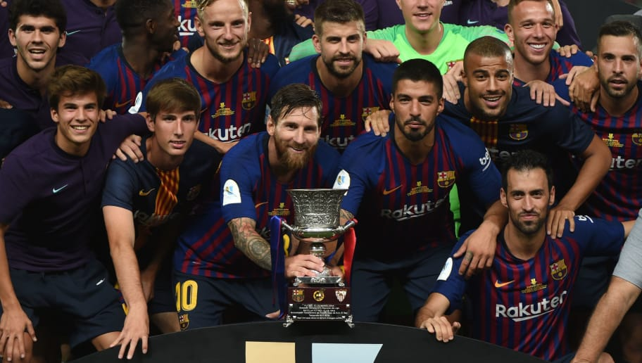 Barcelona's Argentinian forward Lionel Messi (C) carries the cup as they celebrate at the end of the Spanish Super Cup final between Sevilla FC and FC Barcelona at Ibn Batouta Stadium in the Moroccan city of Tangiers on August 12, 2018. - Barcelona defeated Sevilla 2-1 to win the Spanish Super Cup. (Photo by FADEL SENNA / AFP)        (Photo credit should read FADEL SENNA/AFP/Getty Images)