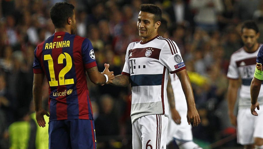 Barcelona's midfielder Rafinha (L) shakes hands with his brother Bayern Munich's Spanish midfielder Thiago Alcantara (C) during the UEFA Champions League football match FC Barcelona vs FC Bayern Muenchen at the Camp Nou stadium in Barcelona on May 6, 2015.     AFP PHOTO/ QUIQUE GARCIA / AFP PHOTO        (Photo credit should read /AFP/Getty Images)