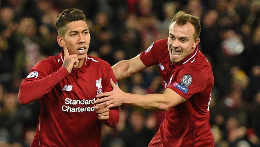 Liverpool's Brazilian midfielder Roberto Firmino celebrates with Liverpool's Swiss midfielder Xherdan Shaqiri (R) after scoring the opening goal of the UEFA Champions League group C football match between Liverpool and Red Star Belgrade at Anfield in Liverpool, north west England on October 24, 2018. (Photo by Oli SCARFF / AFP)        (Photo credit should read OLI SCARFF/AFP/Getty Images)