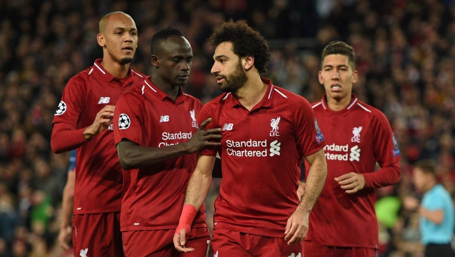 Liverpool's Egyptian midfielder Mohamed Salah (2nd R) celebrates with Liverpool's Senegalese striker Sadio Mane (2nd L) and Liverpool's Brazilian midfielder Fabinho (L) after scoring their third goal from the penalty spot during the UEFA Champions League group C football match between Liverpool and Red Star Belgrade at Anfield in Liverpool, north west England on October 24, 2018. (Photo by Oli SCARFF / AFP)        (Photo credit should read OLI SCARFF/AFP/Getty Images)