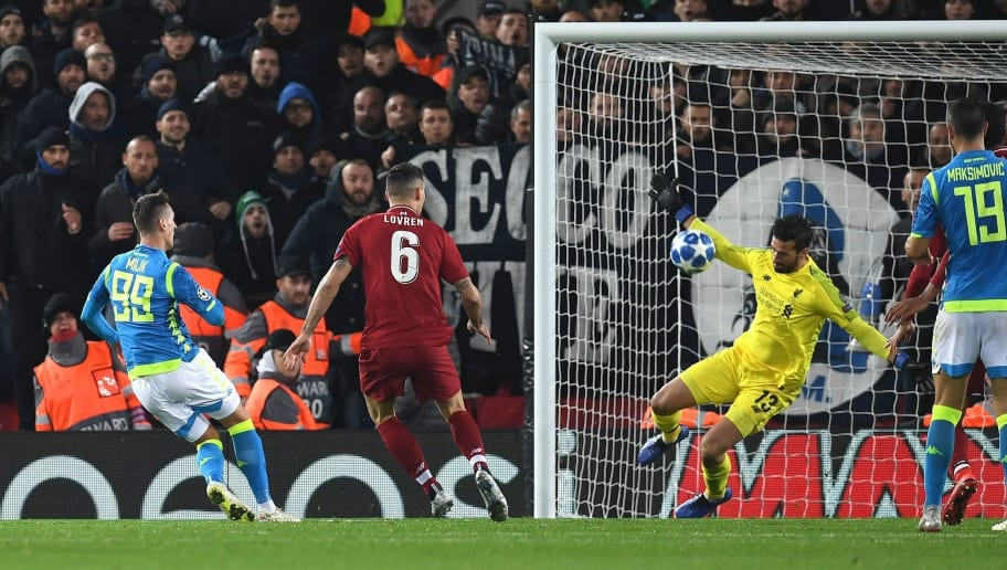 Liverpool's Brazilian goalkeeper Alisson Becker (2R) saves a shot from Napoli's Polish striker Arkadiusz Milik (L) during the UEFA Champions League group C football match between Liverpool and Napoli at Anfield stadium in Liverpool, north west England on December 11, 2018. (Photo by Paul ELLIS / AFP)        (Photo credit should read PAUL ELLIS/AFP/Getty Images)