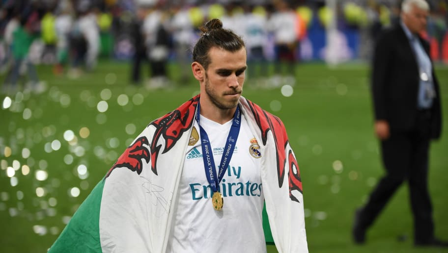 Real Madrid's Welsh forward Gareth Bale with his winner's medal and a Welsh flag on the pitch as Real Madrid players celebrate winning the UEFA Champions League final football match between Liverpool and Real Madrid at the Olympic Stadium in Kiev, Ukraine on May 26, 2018. - Real Madrid defeated Liverpool 3-1. (Photo by Paul ELLIS / AFP)        (Photo credit should read PAUL ELLIS/AFP/Getty Images)