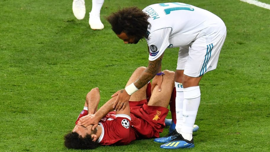 Real Madrid's Brazilian defender Marcelo (R) stands next to Liverpool's Egyptian forward Mohamed Salah laying on the pitch after injury during the UEFA Champions League final football match between Liverpool and Real Madrid at the Olympic Stadium in Kiev, Ukraine on May 26, 2018. (Photo by Sergei SUPINSKY / AFP)        (Photo credit should read SERGEI SUPINSKY/AFP/Getty Images)