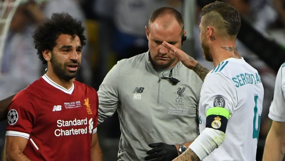 Real Madrid's Spanish defender Sergio Ramos (R) comes over to console Liverpool's Egyptian forward Mohamed Salah (L) who has been forced the leave the pitch after hurting his shoulder in a challenge with Ramos during the UEFA Champions League final football match between Liverpool and Real Madrid at the Olympic Stadium in Kiev, Ukraine on May 26, 2018. (Photo by Paul ELLIS / AFP)        (Photo credit should read PAUL ELLIS/AFP/Getty Images)