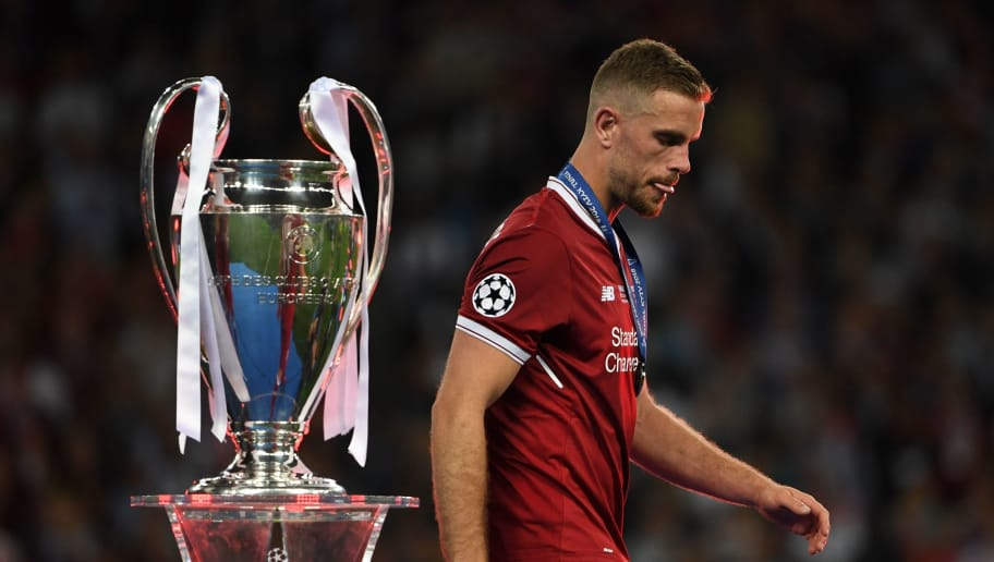 Liverpool's Liverpool's English midfielder Jordan Henderson walks past the trophy as he collects his loser's medal after the UEFA Champions League final football match between Liverpool and Real Madrid at the Olympic Stadium in Kiev, Ukraine on May 26, 2018. - Real Madrid defeated Liverpool 3-1. (Photo by Paul ELLIS / AFP)        (Photo credit should read PAUL ELLIS/AFP/Getty Images)