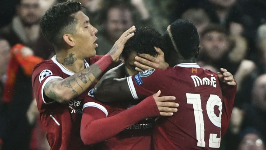 Liverpool's Egyptian midfielder Mohamed Salah (C) celebrates with Liverpool's Brazilian midfielder Roberto Firmino and Liverpool's Senegalese midfielder Sadio Mane (R) after scoring during the UEFA Champions League first leg semi-final football match between Liverpool and Roma at Anfield stadium in Liverpool, north west England on April 24, 2018. (Photo by Filippo MONTEFORTE / AFP)        (Photo credit should read FILIPPO MONTEFORTE/AFP/Getty Images)
