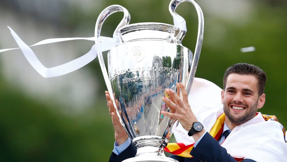 Real Madrid's Spanish defender Nacho Fernandez celebrates holding the trophy at Cibeles square in Madrid on May 27, 2018 after Real Madrid won their third Champions League title in a row in Kiev. (Photo by BENJAMIN CREMEL / AFP)        (Photo credit should read BENJAMIN CREMEL/AFP/Getty Images)