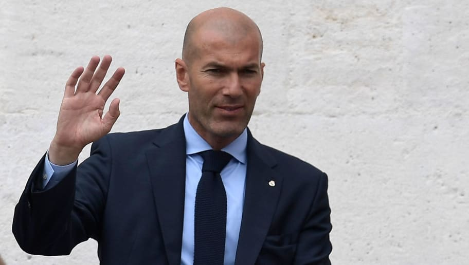 Real Madrid's French coach Zinedine Zidane (L) and Real Madrid's Spanish midfielder Daniel Ceballos greet supporters from the balcony of the headquarters of the regional government of Madrid at the Puerta del Sol square in Madrid on May 27, 2018 as they celebrate their third Champions League title in a row in Kiev. (Photo by OSCAR DEL POZO / AFP)        (Photo credit should read OSCAR DEL POZO/AFP/Getty Images)