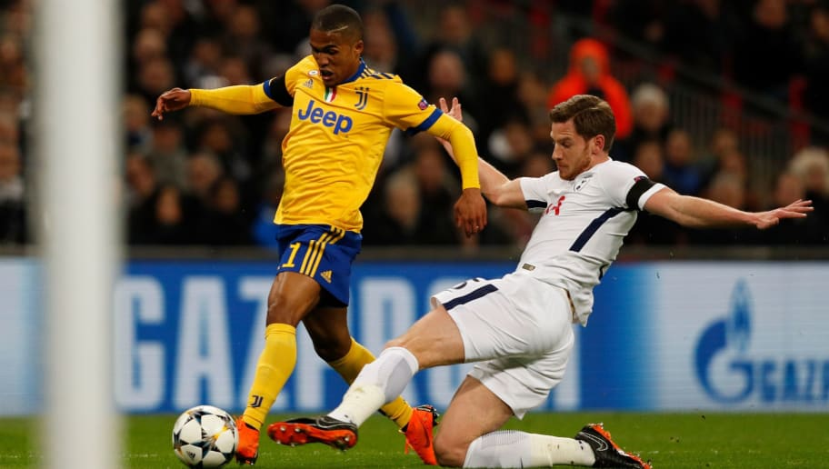Tottenham Hotspur's Belgian defender Jan Vertonghen (R) slides in to attempt a challenge on Juventus' Brazilian midfielder Douglas Costa (L) sparking Juventus appeals for a penalty that was not awarded during the UEFA Champions League round of sixteen second leg football match between Tottenham Hotspur and Juventus at Wembley Stadium in London, on March 7, 2018. / AFP PHOTO / Adrian DENNIS        (Photo credit should read ADRIAN DENNIS/AFP/Getty Images)