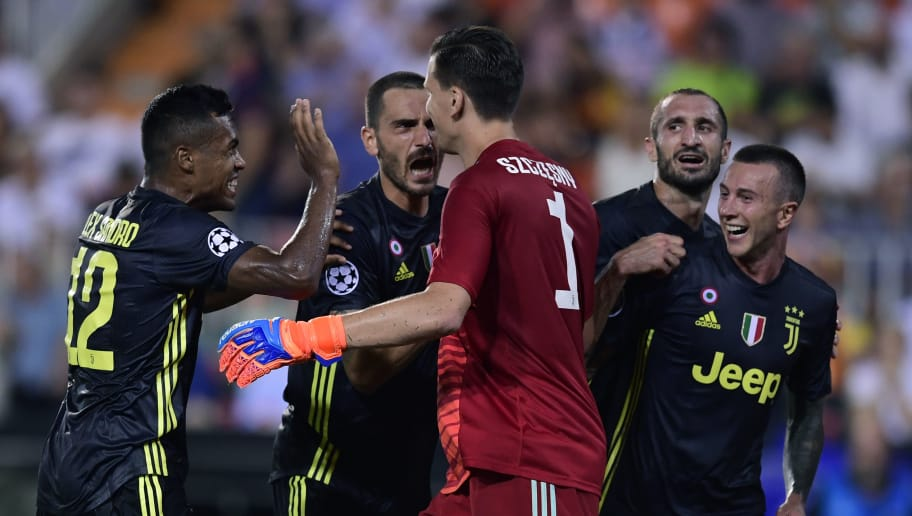 Juventus' Italian goalkeeper Wojciech Szczesny (R) celebrates with Juventus' Italian defender Giorgio Chiellini, Juventus' Italian midfielder Federico Bernardeschi and Juventus' Brazilian defender Alex Sandro after stopping a penalty during the UEFA Champions League group H football match between Valencia CF  and Juventus FC at the Mestalla stadium in Valencia on September 19, 2018. (Photo by JAVIER SORIANO / AFP)        (Photo credit should read JAVIER SORIANO/AFP/Getty Images)