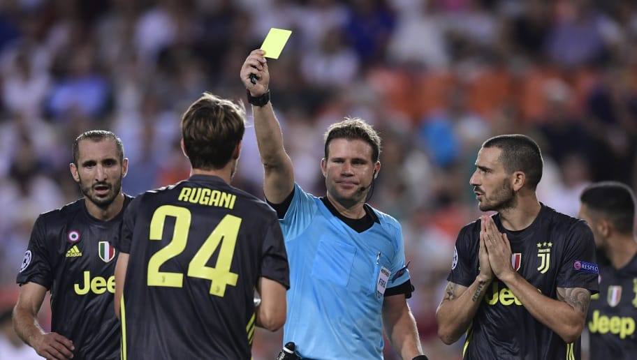 Referee Felix Brych shows a yellow card to Juventus' Italian defender Daniele Rugani during the UEFA Champions League group H football match between Valencia CF  and Juventus FC at the Mestalla stadium in Valencia on September 19, 2018. (Photo by JAVIER SORIANO / AFP)        (Photo credit should read JAVIER SORIANO/AFP/Getty Images)