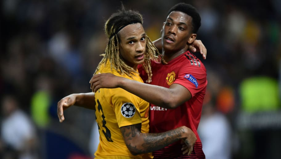 Manchester United's French striker Anthony Martial (R) and Young Boys Swiss defender Kevin Mbabu embrace after the UEFA Champions League group H football match between Young Boys and Manchester United at The Stade de Suisse in Bern on September 19, 2018. (Photo by Fabrice COFFRINI / AFP)        (Photo credit should read FABRICE COFFRINI/AFP/Getty Images)